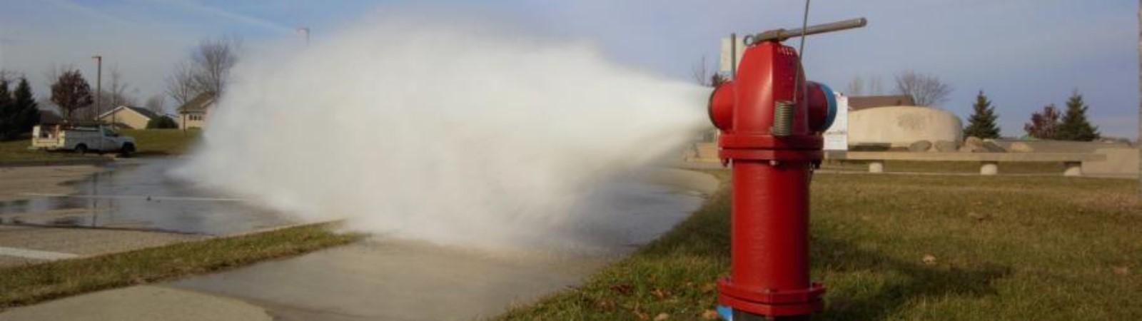 Open fire hydrant spraying water during flushing
